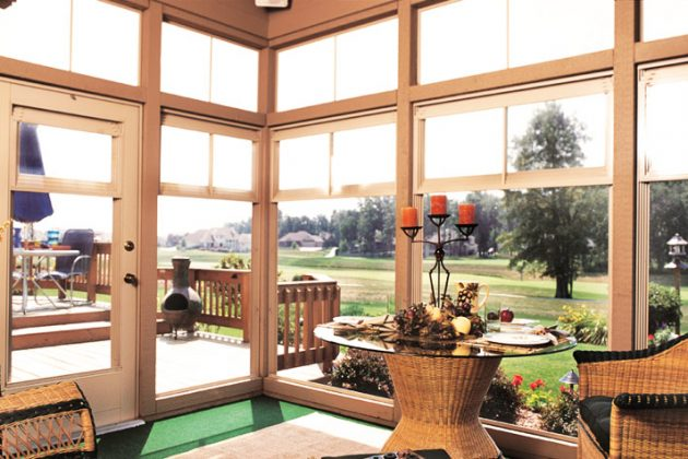 Gulf Coast sun room by Backyard Paradis overlooking the golf course with wicker furniture inside.