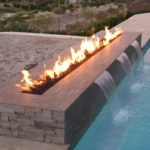 Cool horizontal fire pit by the pool built by Backyard Paradise Inc.