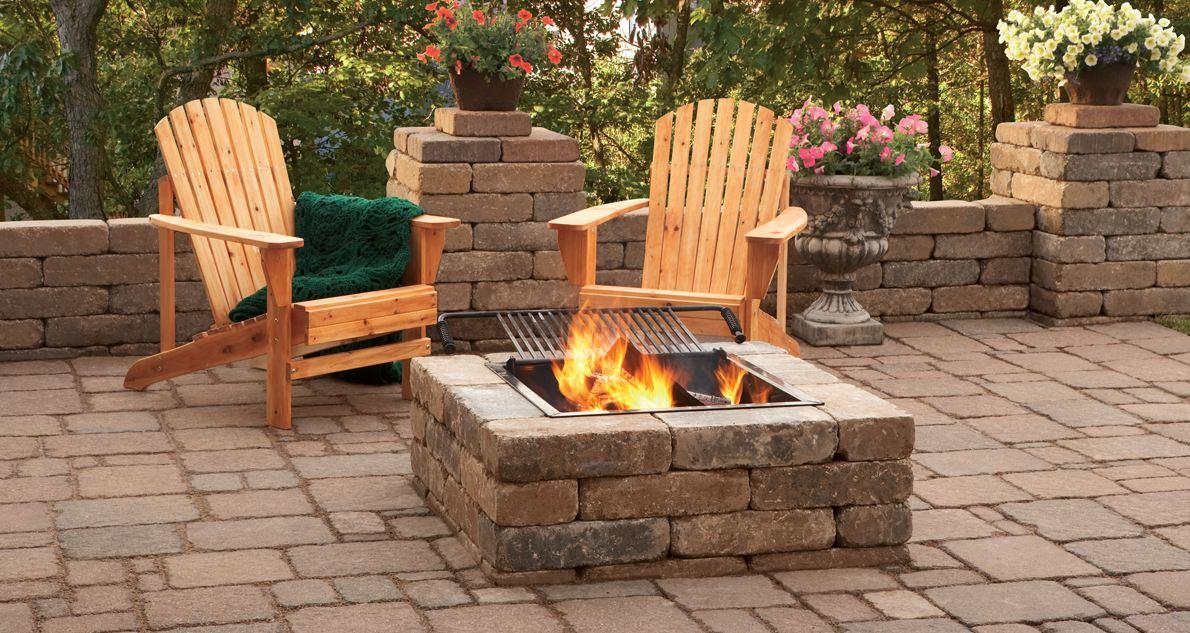 Beautiful fire pit with adirondack chairs and green blanket.