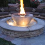 Gulf Coast fire pit with water feature by Backyard Paradise Inc.