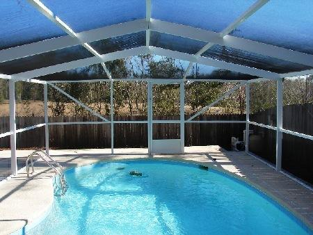 Gulf Coast pool enclosure with modified hip roof by Backyard Paradise Inc.