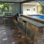 New outdoor kitchen by Backyard Paradise Inc with pool in background all under a pool enclosure.
