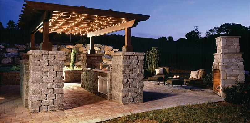 An outdoor kitchen with arbor and lights at night by Backyard Paradise.