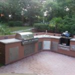 An outdoor kitchen by Backyard Paradise Inc. with brick floors, a stainless steel grill and more.