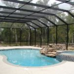 Large pool enclosure with swimming pool, hot tub and rock feature underneath.