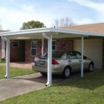 Beautiful car port at a Gulf Coast home wth a silver car underneath.